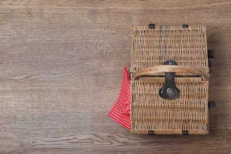 Zamknięty wiklinowy kosz piknikowy na drewnianym stole, widok z góry. Miejsce na tekst