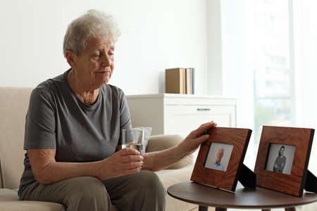 Elderly woman with framed photos at home Stock fotó