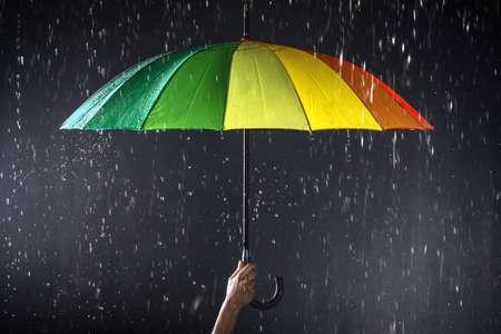 Mujer sosteniendo paraguas brillante bajo la lluvia sobre fondo oscuro, primer plano Foto de archivo