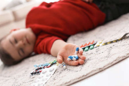 Unconscious little child with pills lying on floor at home. Household danger