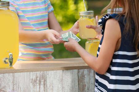 Little girl selling natural lemonade to kid in park, closeup. Summer refreshing drink