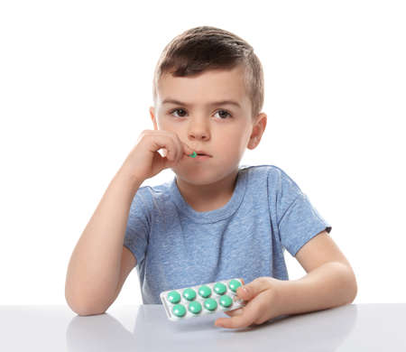 Little child taking pill on white background. Household danger