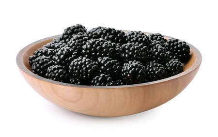 Wooden bowl of tasty ripe blackberries on white background