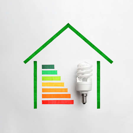 Colorful chart and lamp bulb on white background, top view. Energy efficiency concept