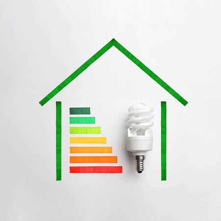 Gráfico de colores y bombilla de lámpara sobre fondo blanco, vista superior. Concepto de eficiencia energética Foto de archivo