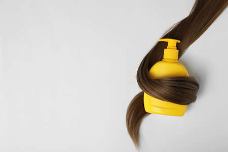 Shampoo bottle wrapped in lock of hair isolated on white, top view. Natural cosmetic products 스톡 콘텐츠