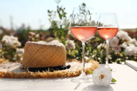 Glasses of rose wine, straw hat and beautiful flower on white wooden table outdoors. Space for text Archivio Fotografico