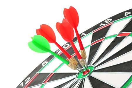 Dart board with color arrows hitting target, closeup Imagens