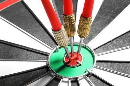 Dart board with red arrows hitting target, closeup