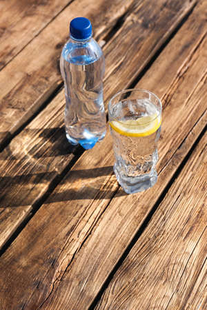Glass and bottle of refreshing drink for hot summer day on wooden table, space for text