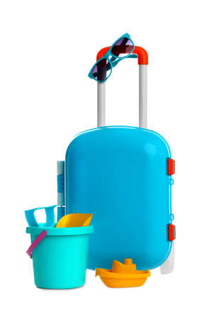 Stylish little blue suitcase with sunglasses and toys on white background