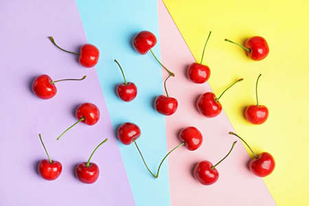 Flat lay composition with sweet cherries on color background