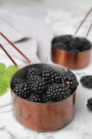 Metal saucepans with ripe blackberries on marble table