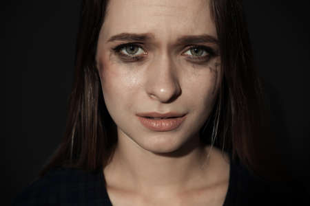 Crying young woman on dark background. Stop violence Stock Photo