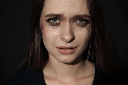 Weinende junge Frau auf dunklem Hintergrund. Stopp Gewalt