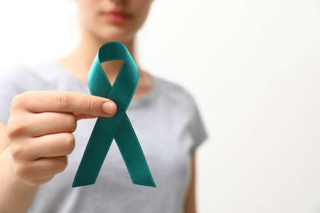 Woman holding teal awareness ribbon against light background, closeup