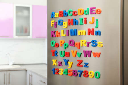 Refrigerator door with colorful magnetic letters and numbers in kitchen. Space for text