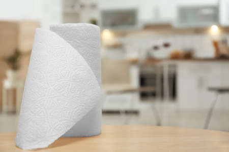 Roll of paper towels on table in kitchen, space for text