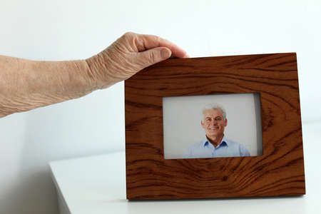 Elderly woman with framed photo of her son indoors, closeup