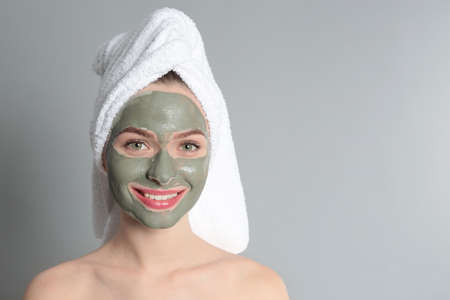 Young woman with clay mask on her face against grey background, space for text. Skin care