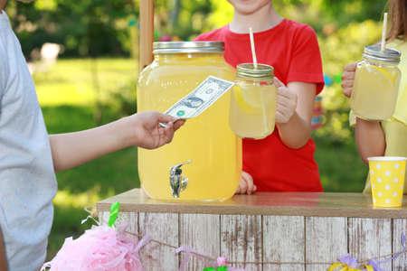 Little girls selling natural lemonade to boy in park, closeup. Summer refreshing drink