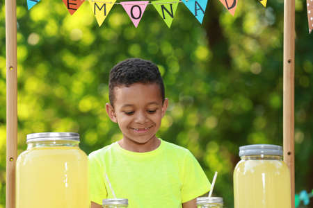 Cute little African-American boy with money at lemonade stand in park. Summer refreshing natural drink Stockfoto