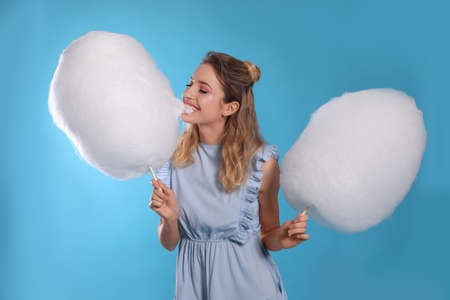 Portrait of pretty young woman with cotton candy on blue background Reklamní fotografie