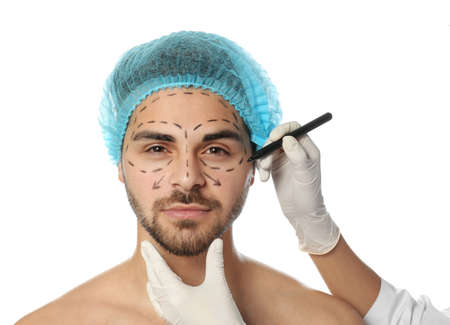 Doctor drawing marks on man's face for cosmetic surgery operation against white background