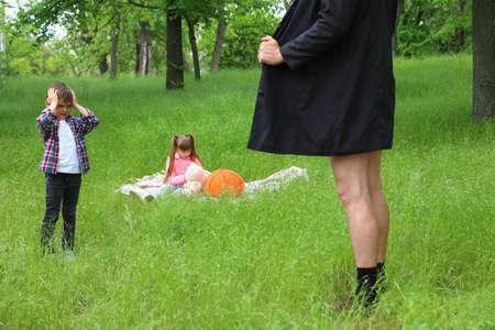Esibizionista maschio aprendo il cappotto davanti ai bambini all'aperto. Bambino in pericolo