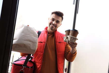 Portrait of courier with order at open door. Food delivery service