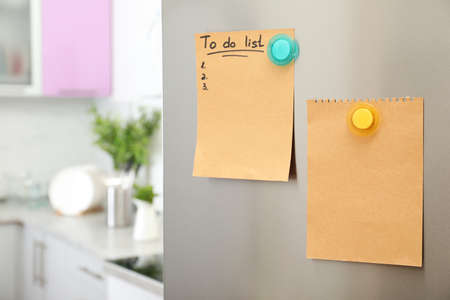 To do list and empty sheet of paper with magnets on refrigerator door in kitchen. Space for text