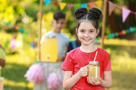 Cute little girl with natural lemonade in park, space for text. Summer refreshing drink
