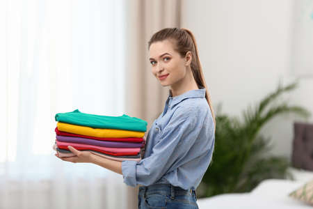 Woman holding folded clean clothes in bedroom. Laundry day