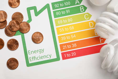 Coins and light bulbs on energy efficiency rating chart, top view Banco de Imagens