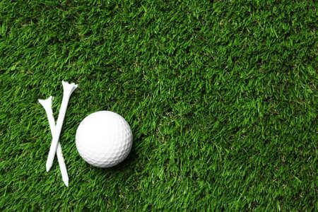 Golfball und Tees auf Kunstrasen, Draufsicht mit Platz für Text