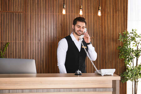 Receptionist talking on phone at desk in lobby