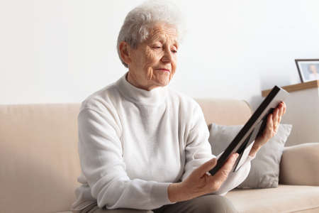 Elderly woman with framed photo on sofa at home Banque d'images
