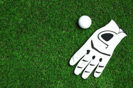 Golf ball and glove on artificial grass, top view with space for text