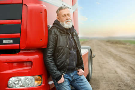 Portrait of mature driver at modern truck outdoors. Space for text