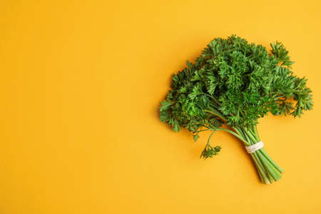 Bunch of fresh green parsley on orange background, top view. Space for text 免版税图像