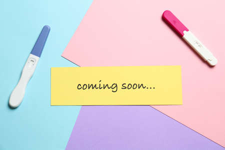 Card with words COMING SOON and pregnancy tests on color background, flat lay