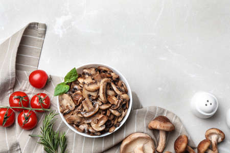 Flat lay composition with delicious cooked mushrooms on white marble table. Space for text