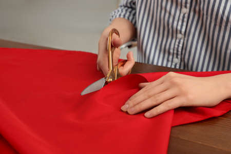 Woman cutting fabric with sharp scissors at wooden table, closeup. Space for text Stock fotó