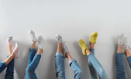 Mujeres jóvenes en zapatos modernos sobre fondo blanco, primer plano Foto de archivo