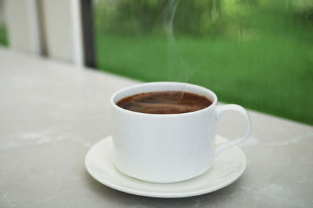 Cup of hot aromatic coffee on white wooden windowsill. Rainy weather Stock Photo