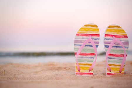 Stijlvolle slippers op zand in de buurt van zee, ruimte voor tekst. Strandaccessoires