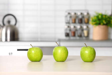Fresh green apples on kitchen counter. Space for text Фото со стока