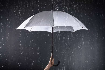 Woman holding white umbrella under rain on dark background, closeup
