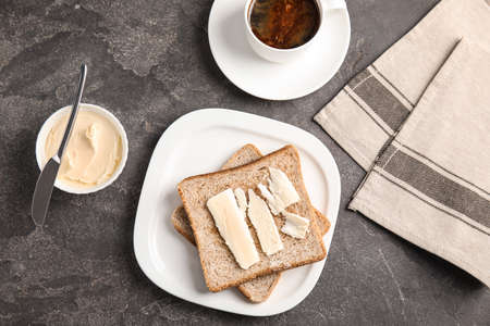 Flat lay composition with bread and butter served on grey table Stock Photo