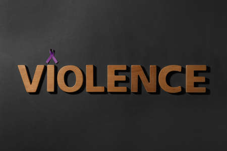Purple awareness ribbon and word VIOLENCE made of wooden letters on black background, top view